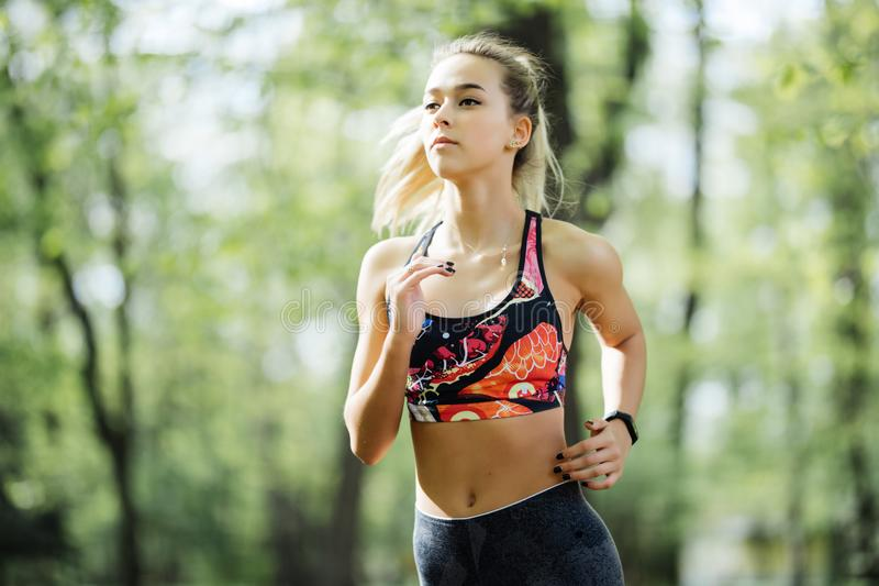 Running woman in park in summer training. Young sport fitness model in sporty running clothes. stock photography