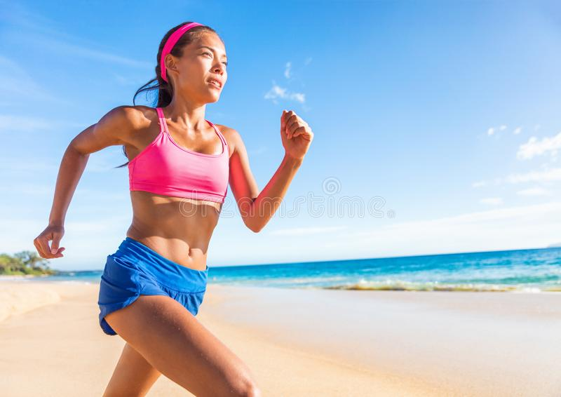 Running woman runner on beach fitness Asian girl training cardio. Weight loss active healthy lifestyle in summer outdoors. Working out sprnting royalty free stock photo
