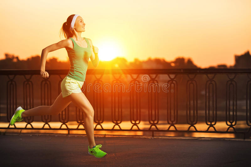 Running woman. Runner is jogging in sunny bright light on sunrise. Female fitness model training outside in the city on a quay. royalty free stock photos