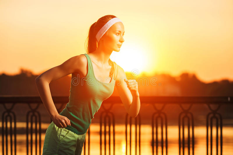 Running woman. Runner is jogging in sunny bright light on sunrise. Female fitness model training outside in the city on a quay. royalty free stock photo