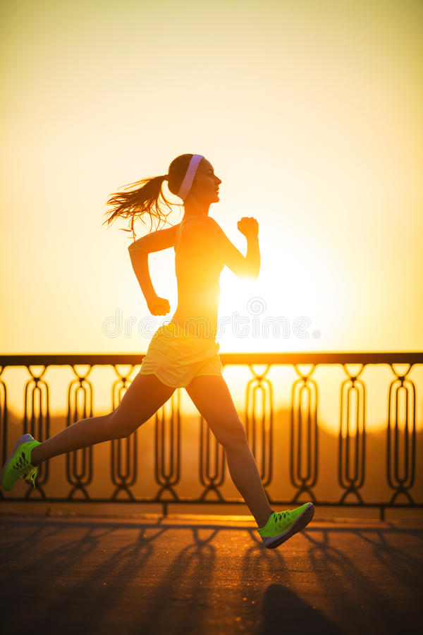 Running woman. Runner is jogging in sunny bright light on sunrise. Female fitness model training outside in the city on a quay. stock images