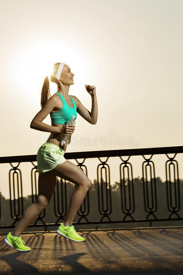 Running woman. Runner is jogging on sunrise. Female fitness mode stock photography