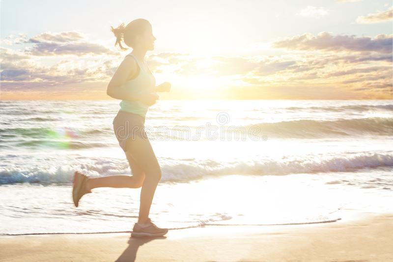 Running woman on sea beach, motion. Girl jogging on sea coast in summer sunny morning. Fitness. Healthy lifestyle royalty free stock photography