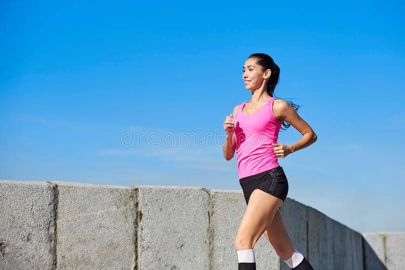 Running woman on urban city. Morning jogging. The athlete trains royalty free stock photography