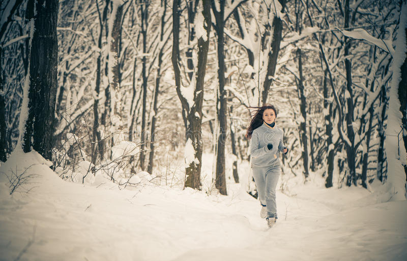 Running woman at winter forest royalty free stock photography