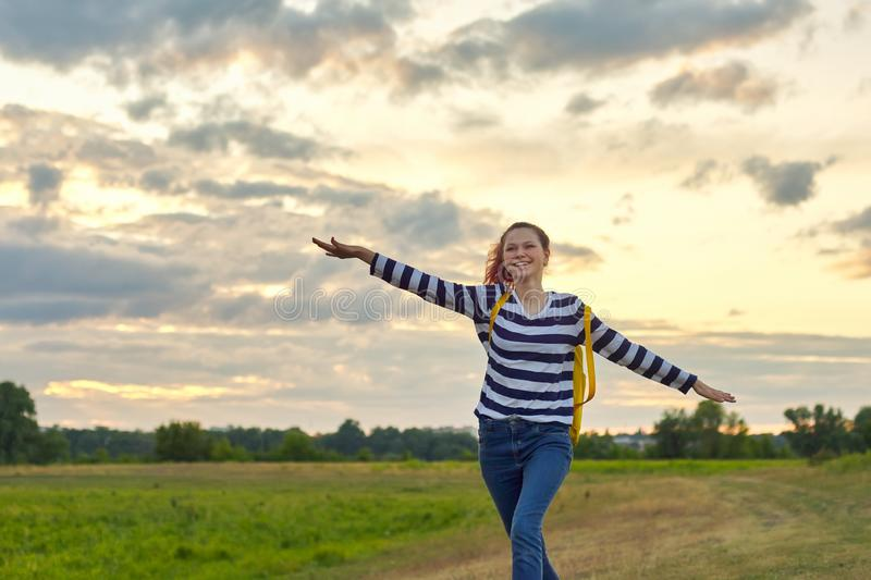 Running young girl with yellow backpack, with open hands stock photo