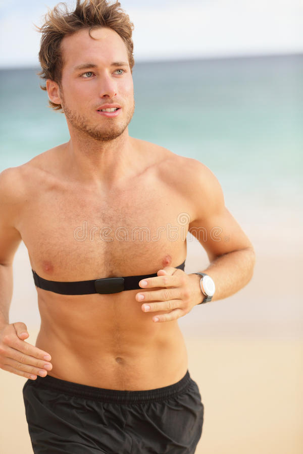 Running young man jogging on beach. Handsome shirtless male runner working out outside by the ocean wearing heart rate monitor. Closeup upper body portrait of stock photo