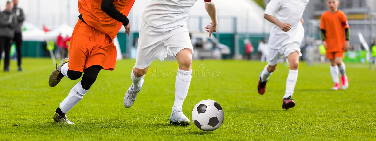 Running Young Soccer Football Players. Footballers Kicking Football Match Game. Youth Soccer Players Running After the Ball. Coach and Soccer Stadium in the stock photography