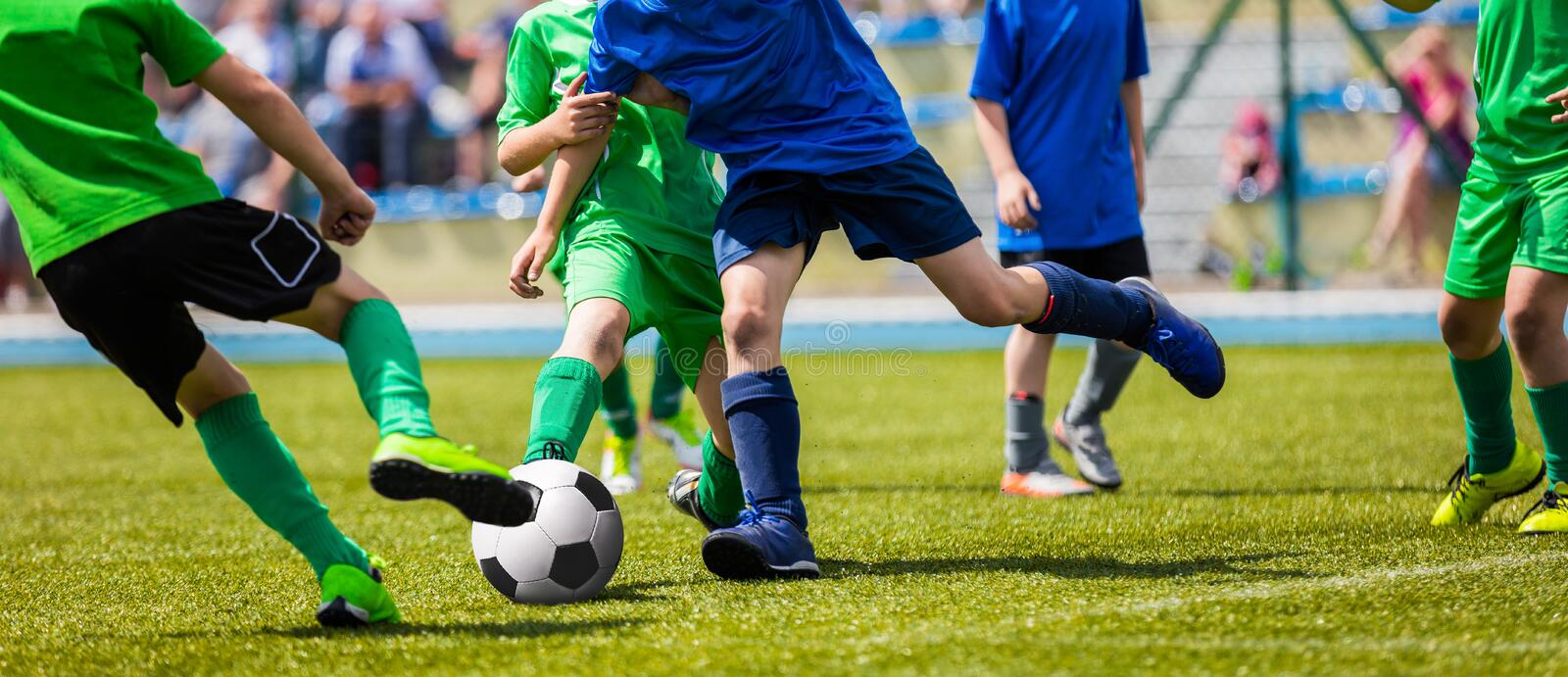 Running Young Soccer Football Players. Footballers Kicking Football Match Game. Youth Soccer Players Running After the Ball. Soccer Stadium in the Background royalty free stock photos