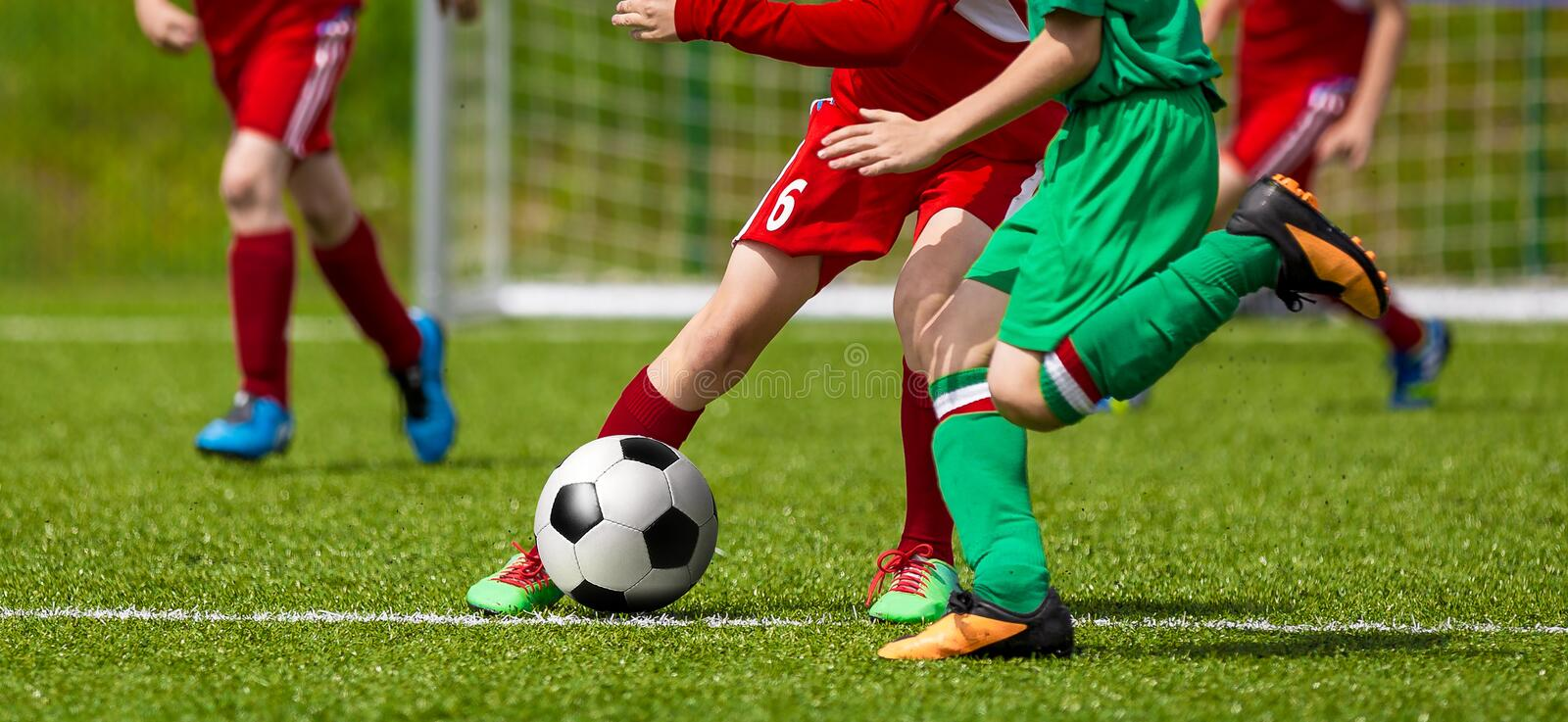 Running Young Soccer Football Players. Footballers Kicking Football Match Game. Youth Soccer Players Running the Ball. Soccer Teams School Tournament royalty free stock image