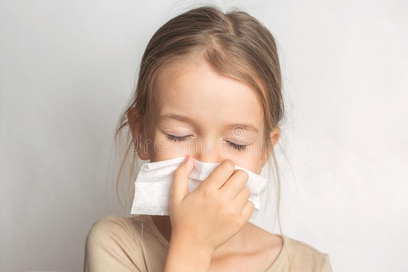 Runny nose in children. A child blows his nose in a handkerchief.  royalty free stock photo