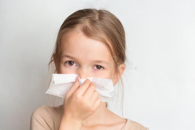 Runny nose in children. A child blows his nose in a handkerchief. Runny nose in children. A child blows his nose in a handkerchief royalty free stock photos