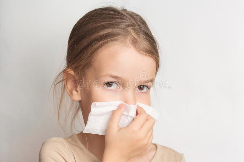 Runny nose in children. A child blows his nose in a handkerchief.  stock image