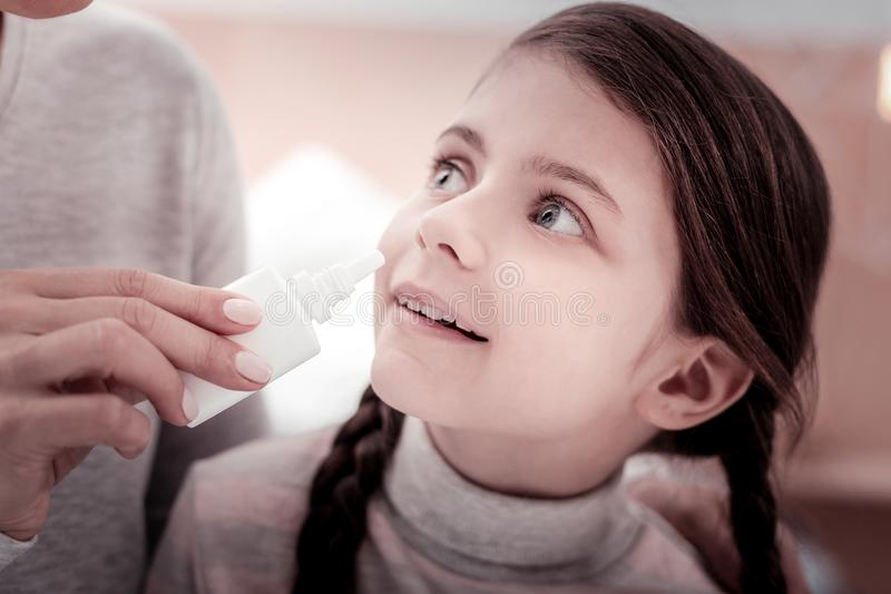 Close up of delighted child with nasal drops stock image