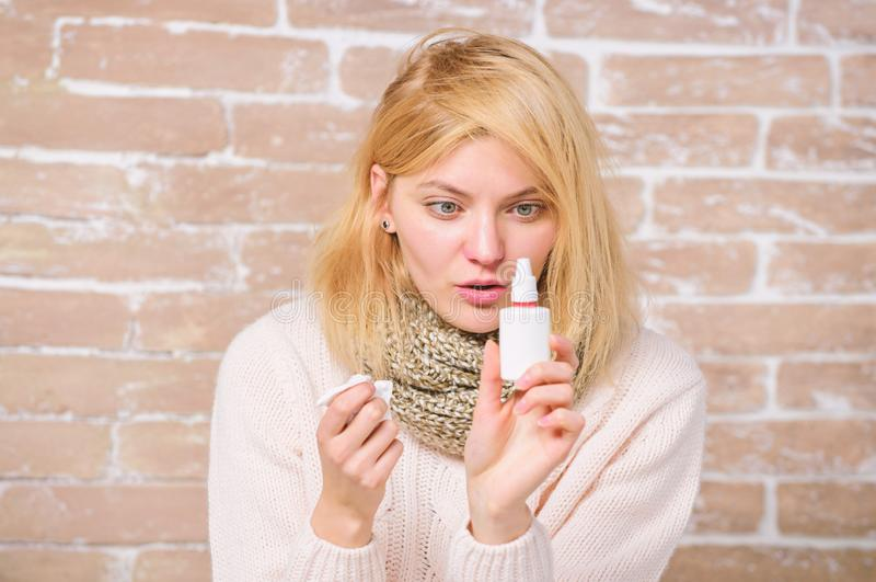 Runny nose and other symptoms of cold. Nasal spray runny nose remedy. Girl sick person hold nasal drops and tissue. Allergy concept. Home treatment. Nasal royalty free stock photo
