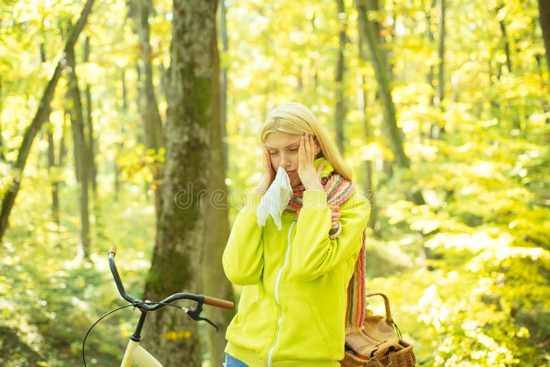 Runny nose remedies. Woman handkerchief sneezing because of allergy. Blonde allergic reaction relax forest. Girl bicycle stock photo