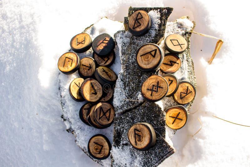 Runor som snidas från trä på snön - fläder Futhark arkivbild