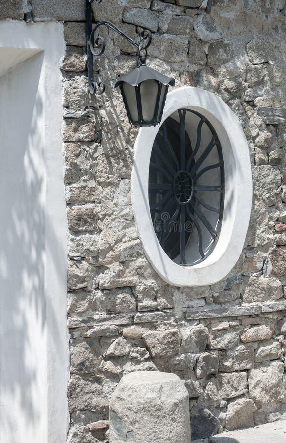 Runt fönster på stenhus royaltyfri bild
