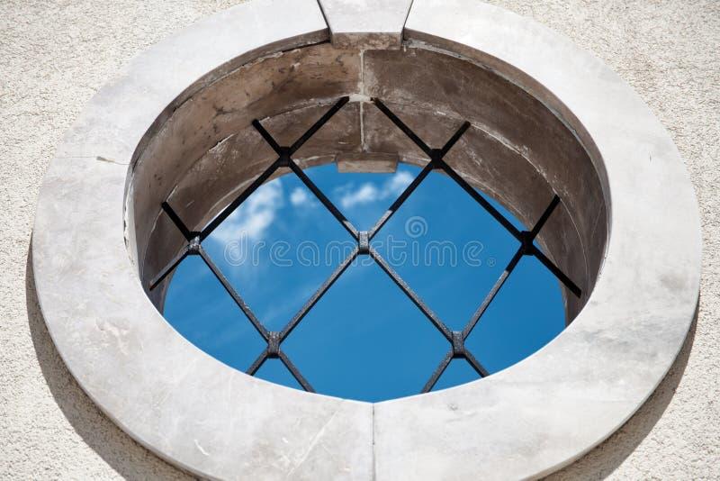 Runt medeltida fönster med sikten för blå himmel för stänger - abstrakt begreppsbakgrund - inomhus utomhus begrepp - runt fönster arkivbild