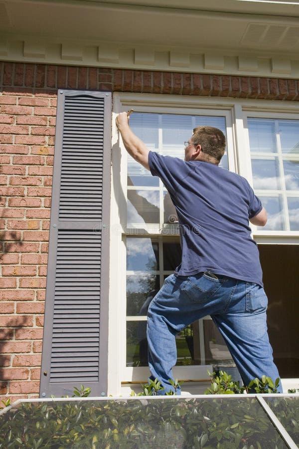 runt om fönster för klippning för dörrmålaremålning royaltyfri fotografi