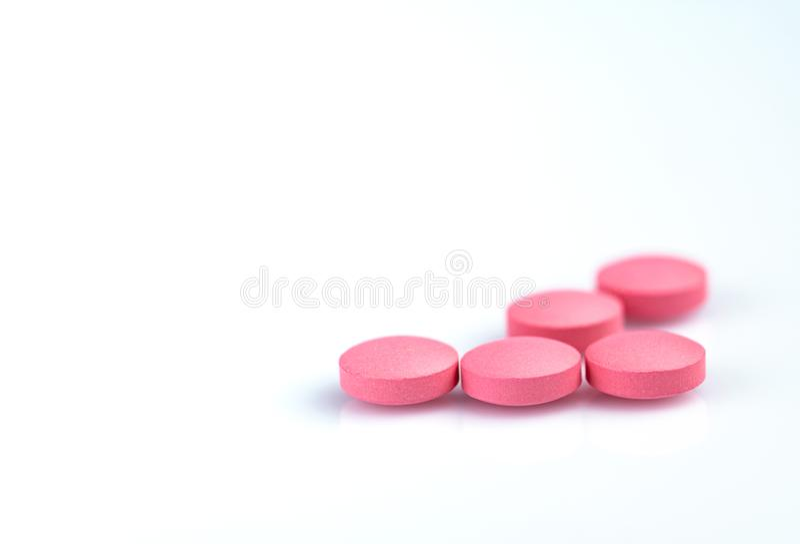 Runt rosa minnestavlapiller på vit bakgrund Vitaminer och mineraler plus folsyravitamin E och zink i drogflaska fotografering för bildbyråer