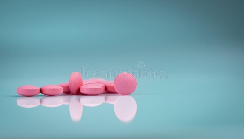 Runt rosa minnestavlapiller p? lutningbakgrund Vitaminer och mineraler plus folsyravitamin E och zink royaltyfri foto