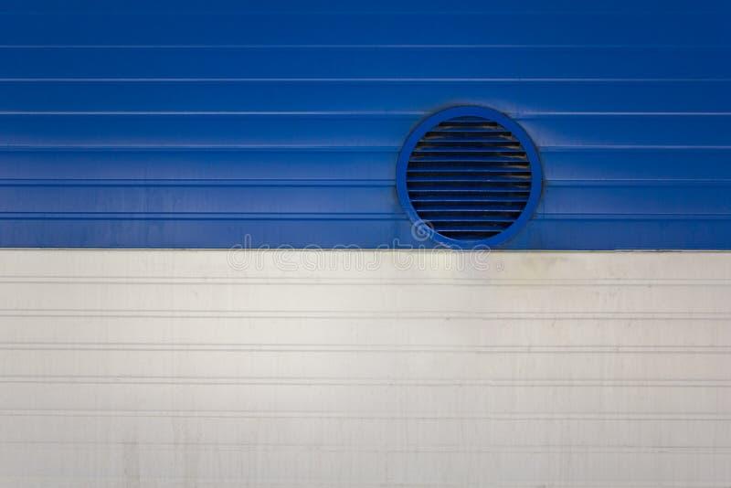 Runt ventilationsfönster med slutare på en smutsig vit blå metallvägg med horisontallinjer Textur f?r grov yttersida arkivfoto