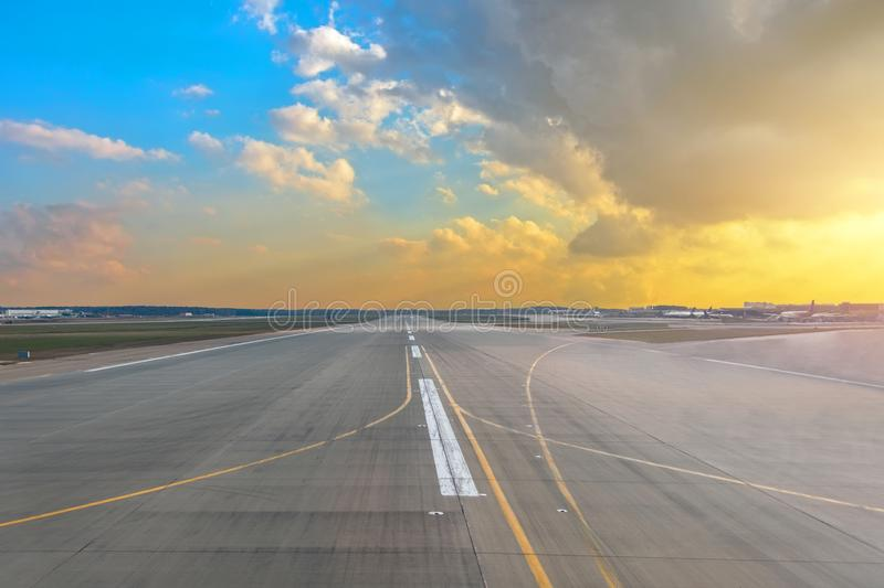 Runway at the airport in the sunset sun light sky blue gradient yellow color cumulus clouds. Runway at the airport in the sunset sun light sky blue gradient stock photography