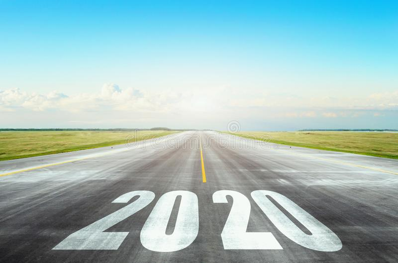Runway asphalt road with the inscription 2020 year with blue sky. The concept of the beginning of new goals and affairs.  stock photo