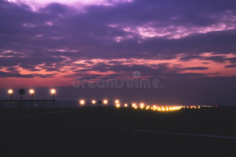 runway lighting systems in sunsed bakground red and purple fa stock
