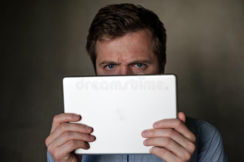Runzeln der ernste reife Mitte gealterte Mann, der Tablette untersucht und sein Gesicht die Stirn lizenzfreies stockbild