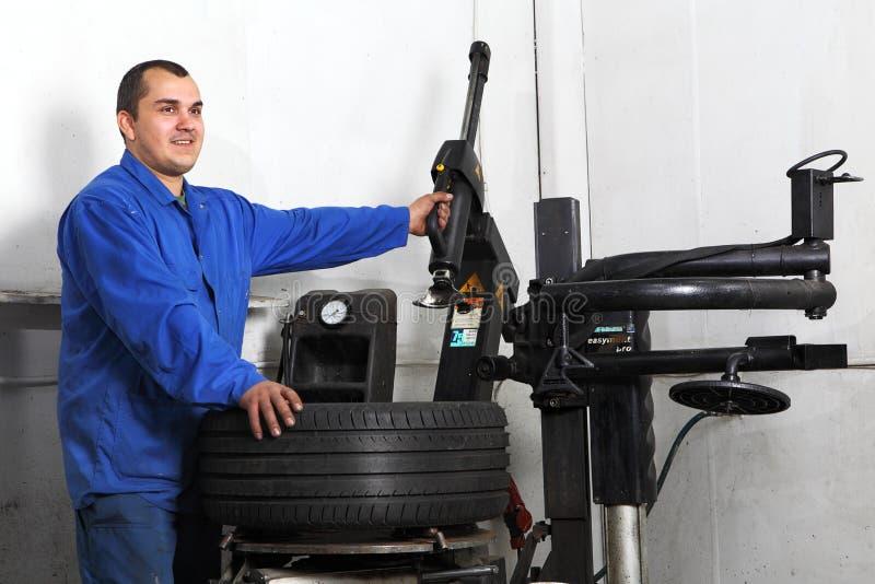 Ruota di automobile automatica dell'automobile di caricamento del riparatore alla macchina del montaggio del pneumatico fotografia stock libera da diritti