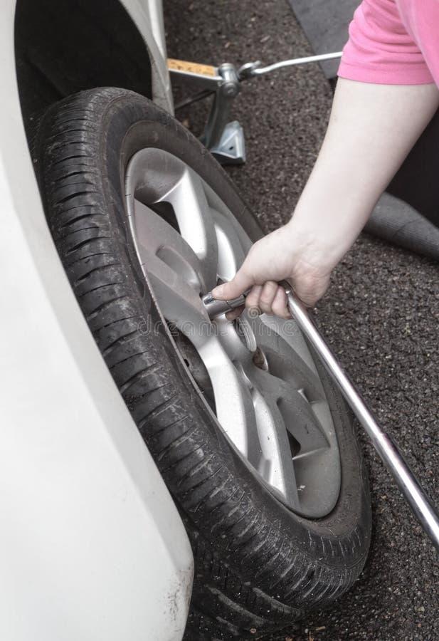 Ruota di cambiamento della donna su un'automobile rotta sulla strada immagini stock