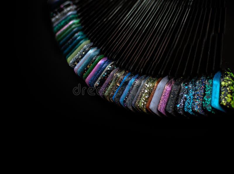 Ruota di colore di arte del chiodo su fondo nero Metta delle unghie e dei campioni artificiali del manicure Vista superiore, spaz fotografia stock