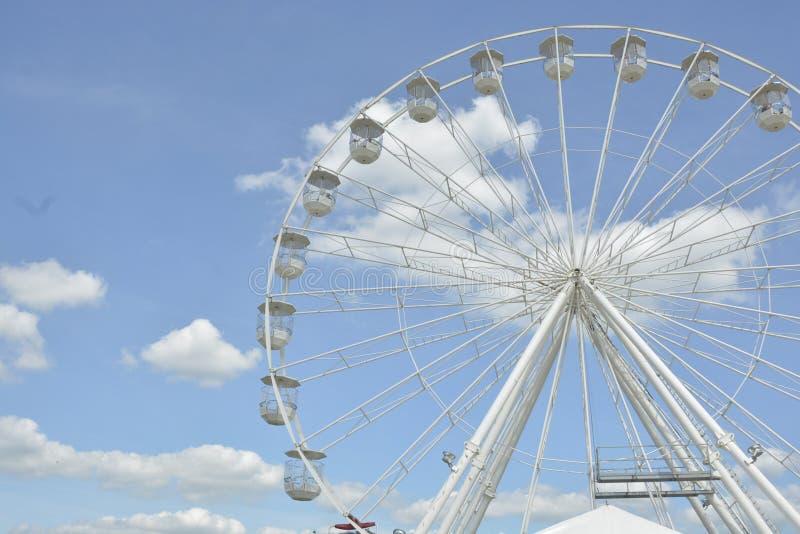 Ruota di ferris bianca del parco di divertimenti nei precedenti del cielo blu fotografia stock