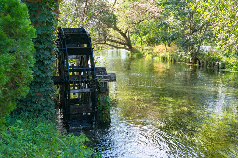 Ruota di mulino a acqua sul fiume fotografia stock