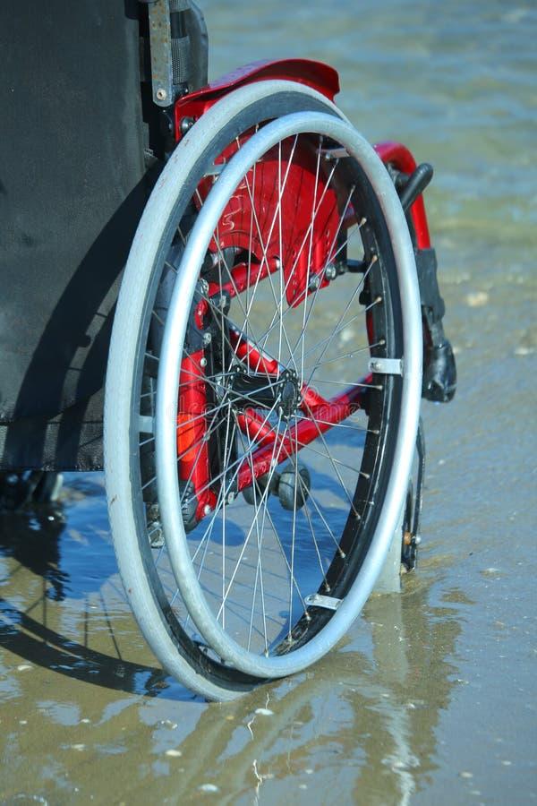 Ruota di una sedia a rotelle sulla riva dal mare fotografia stock libera da diritti