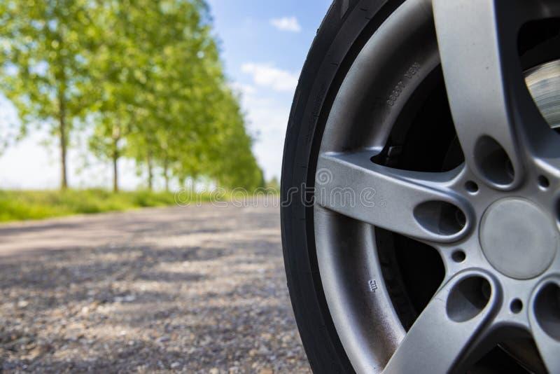 Ruota rurale di sicurezza dell'automobile della strada su Sunny Morning immagini stock