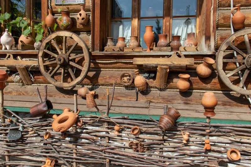 Ruote del carretto e vasi ceramici che appendono su una parete della casa del villaggio Recinto dell'acacia in basso fotografia stock