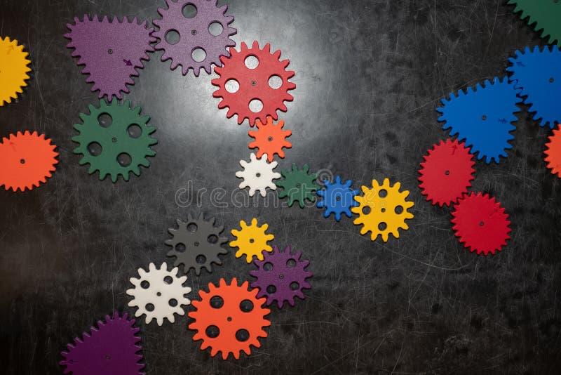 Ruote dentate di plastica del costruttore su fondo di legno scuro Giocattoli popolari Copyspace fotografia stock libera da diritti