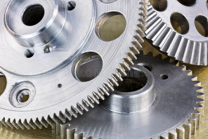 Ruote dentate grige dell'ingranaggio del metallo sul mackintosh industriale graffiato del fondo immagini stock