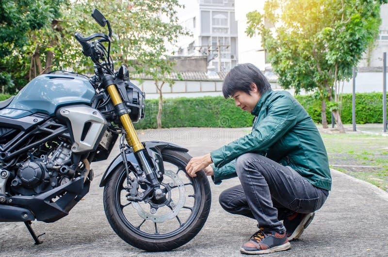 Ruote per portarti ovunque Foto di Handsome rider biker man con giacca di pelle verde che controlla ruote e pneumatici di una mot immagine stock