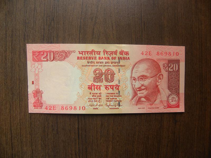 20 rupees India banknote. Obverse of red orange color twenty rupees India banknote with Mahatma Gandhi portrait kept on wooden table royalty free stock image
