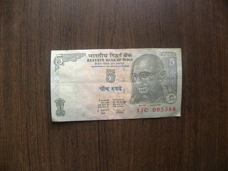 5 rupees India note. Obverse of green color 5 rupees India banknote with Mahatma Gandhi portrait kept on wooden table stock image