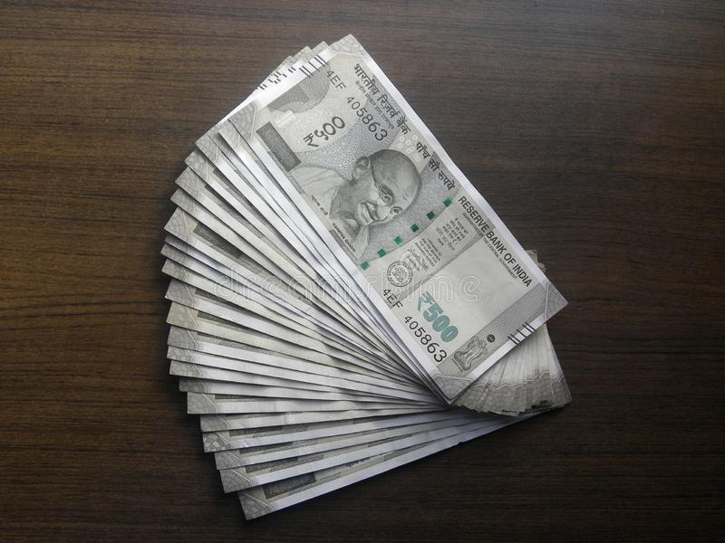 500 Rupees. Many five hundred rupees India currency notes kept on wooden table stock photos