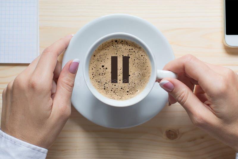 Ruptura de café As mãos fêmeas tocam no copo branco do café clássico, vista superior, fim acima Ícone da pausa na espuma fotografia de stock