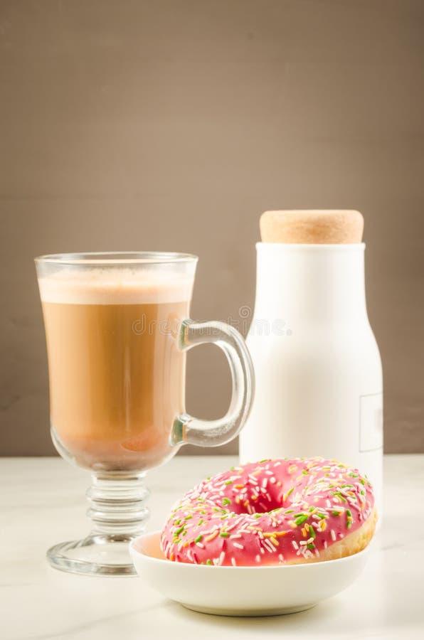 Ruptura de café: cappuccino, filhós cor-de-rosa açucarado fresca e garrafa/ruptura de café brancas: cappuccino, filhós cor-de-ros fotos de stock royalty free