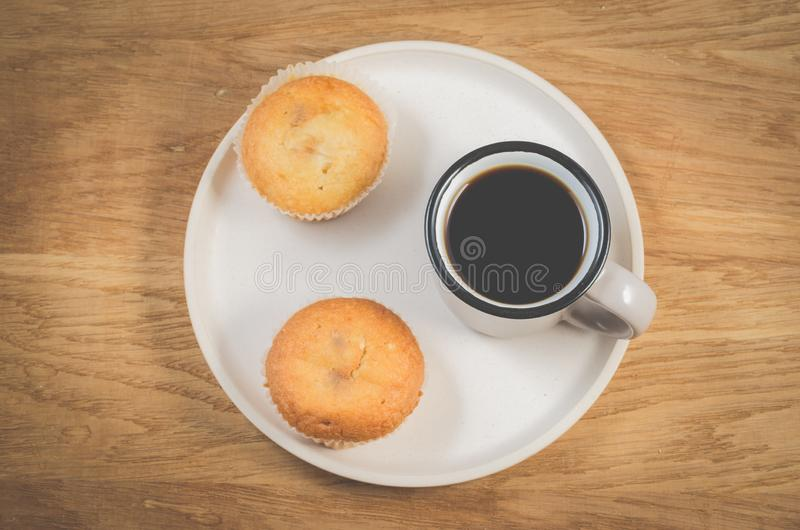 Ruptura de café Copo do café preto e dos queques em uma bandeja branca, tabela de madeira Vista superior Conceito do pequeno almo imagem de stock royalty free