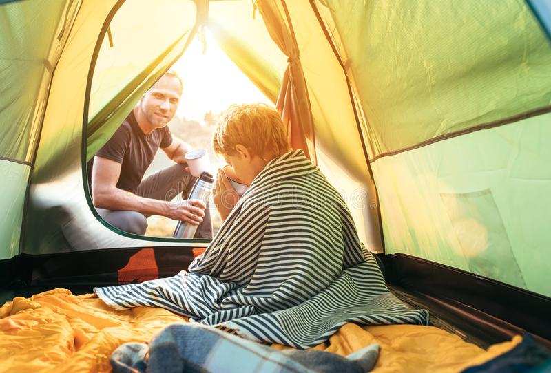 Ruptura de chá na barraca do acampamento: chá quente da bebida do pai e do filho em nivelar o tempo foto de stock