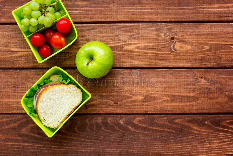 A ruptura saudável com maçã, a uva e o sanduíche na cesta de comida no plano home da tabela colocam o modelo fotografia de stock